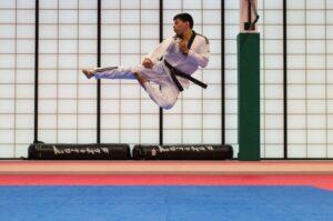 martial artist kicking in the air above a blue mat